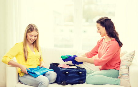 packing suitcase: travel, vacation and friendship concept - two smiling teenage girls packing suitcase at home Stock Photo
