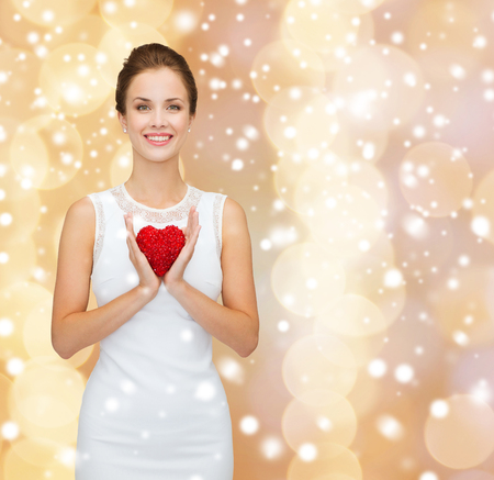 hands holding heart: happiness, health, charity and love concept - smiling woman in white dress with red heart over beige background over beige lights background and snow Stock Photo