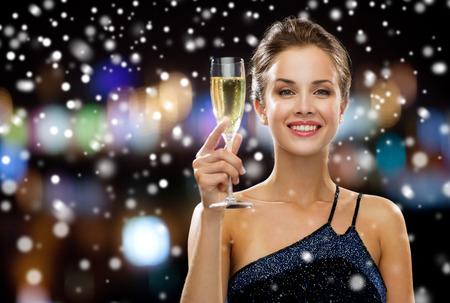 birthday champagne: party, drinks, holidays, christmas and people concept - smiling woman in evening dress with glass of sparkling wine over night lights and snow background