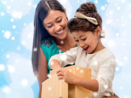 little girl surprised: christmas, holidays, celebration, family and people concept - happy mother and child girl with gift box over blue lights background Stock Photo