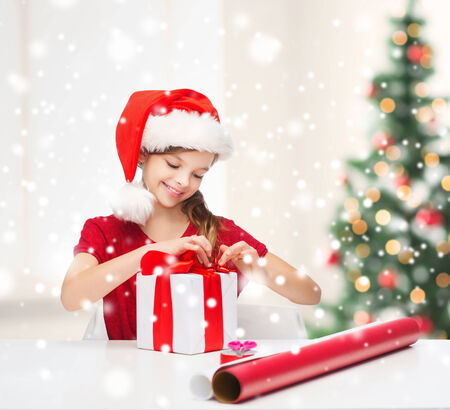 christmas wrapping paper: childhood, decorating and people concept- smiling girl in santa helper hat with gift box, wrapping paper over living room with christmas tree and snow background