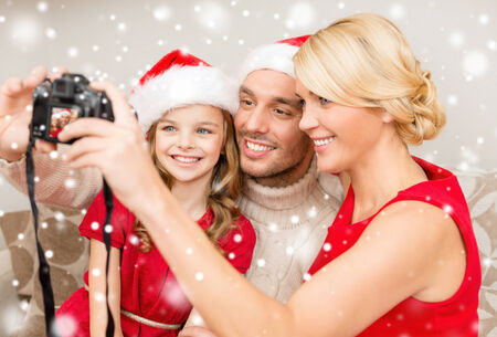 family portrait: christmas, holidays, technology and people concept - happy family with digital camera taking selfie at home