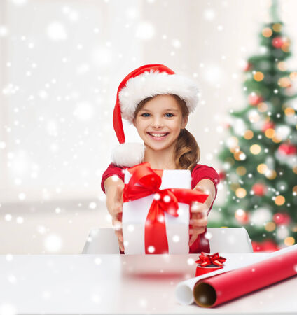 childhood, decorating and people concept- smiling girl in santa helper hat with gift box, wrapping paper over living room with christmas tree and snow  photo