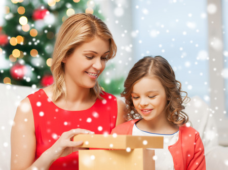 christmas, holidays, people and family concept - smiling mother and daughter opening gift box at home photo