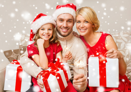 christmas, holidays, happiness and people concept - smiling family in santa helper hats with many gift boxes and sparklers at home Stockfoto