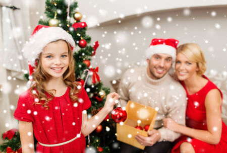 family, christmas, winter holidays, childhood and people concept - smiling family in santa helper hats decorating christmas tree at home photo