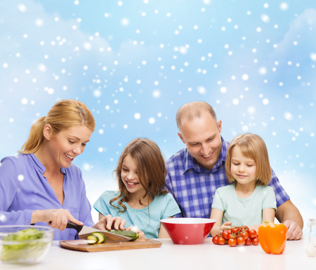food, family, children, happiness and people concept - happy family with two kids making dinner over blue sky and snowflakes  photo