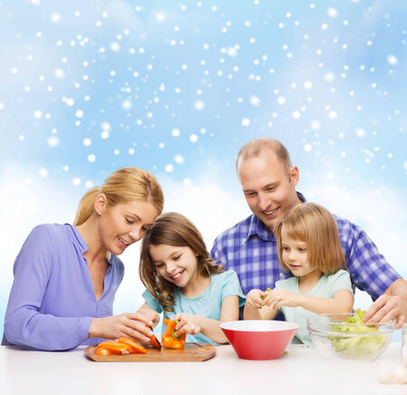 food, family, children, happiness and people concept - happy family with two kids making dinner over blue sky and snowflakes background photo