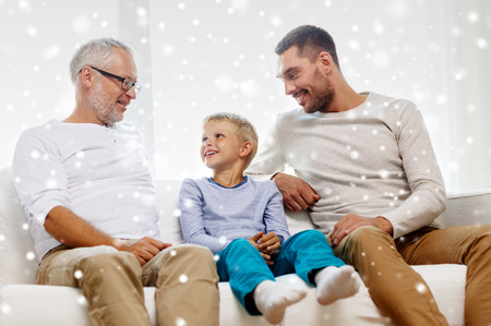 family couch: family, happiness, generation and people concept - smiling father, son and grandfather sitting on couch at home Stock Photo