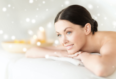 spa towels: beauty, health, people and spa concept - beautiful young woman in spa