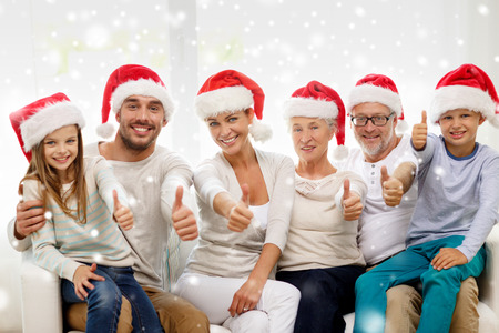 family, happiness, generation, holidays and people concept - happy family in santa helper hats sitting on couch and showing thumbs up gesture at home