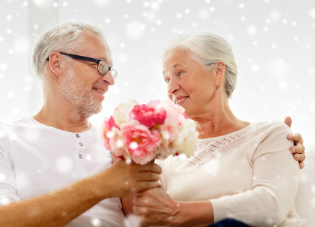 family, holidays, age and people concept - happy senior couple with bunch of flowers at home photo