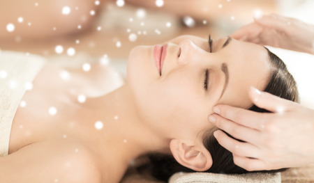 beauty, health, holidays, people and spa concept - beautiful woman in spa salon getting face or head massage Stock Photo