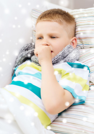 flue season: childhood, healthcare and people concept - ill boy with scarf lying in bed and coughing at home