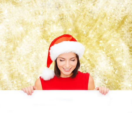 christmas, x-mas, people, advertisement and sale concept - happy woman in santa helper hat with blank white board over yellow lights  photo