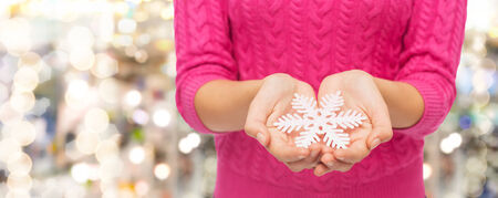 christmas, holidays and people concept - close up of woman in pink sweater holding snowflake over lights background photo