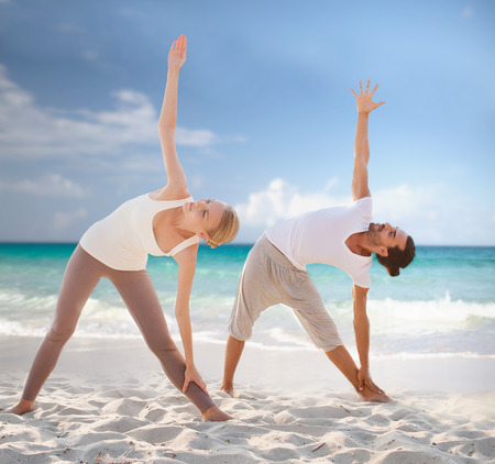 fitness, sport, friendship and lifestyle concept - couple making yoga exercises on summer beach Stock Photo