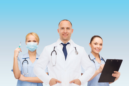 medics: medicine, profession, teamwork and healthcare concept - international group of smiling medics or doctors with clipboard and stethoscopes over blue background