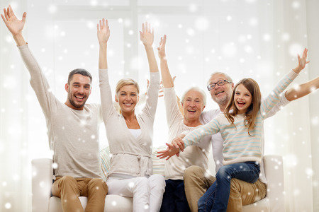 family, happiness, generation and people concept - happy family sitting on sofa and rising hands at home Banque d'images