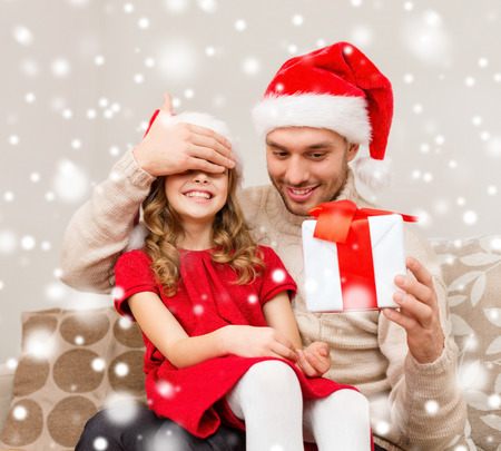 christmas, holidays, family and people concept - smiling father and daughter in santa hats holding gift box and covering eyes at home photo