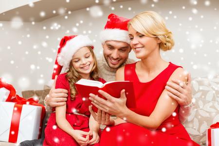 mujer leyendo libro: familia, la Navidad y la gente concepto - sonriendo familia en los sombreros de santa que lee el libro o la biblia en casa