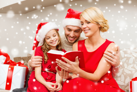 woman reading book: family, christmas and people concept - smiling family in santa hats reading book or bible at home
