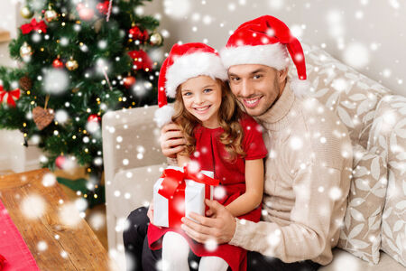 christmas, holidays, family and people concept - smiling father and daughter holding gift box and hugging at home photo