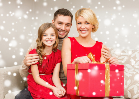 christmas, holidays, happiness and people concept - smiling family with big red gift box at home photo