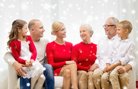family, holidays, generation, christmas and people concept - smiling family sitting on couch at home photo
