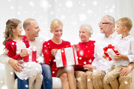 family, holidays, generation, christmas and people concept - smiling family with gift boxes sitting on couch at home photo