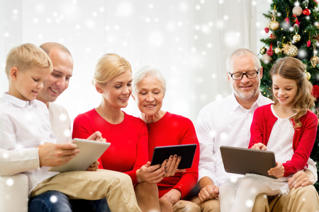 family, holidays, christmas, technology and people concept - smiling family with tablet pc computers sitting on couch at home photo