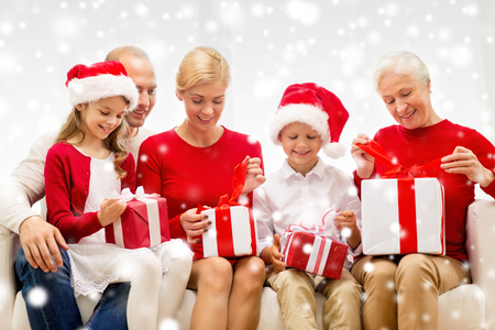 family, holidays, generation, christmas and people concept - smiling family opening gift boxes at home photo