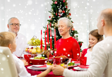 family, holidays, generation, christmas and people concept - smiling family having dinner and praying at home photo