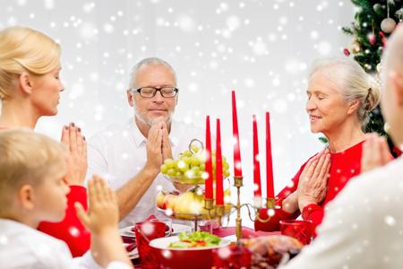 familia orando: familiares, vacaciones, generaci�n, Navidad y la gente concepto - sonriendo familia cenando y orando en casa Foto de archivo