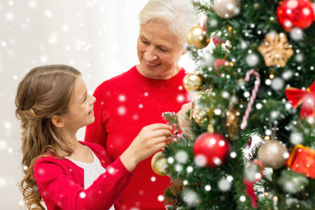 smiling girl with grandmother decorating christmas tree at home photo