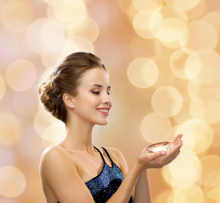 people, holidays and glamour concept - smiling woman in evening dress with diamond over beige lights background photo