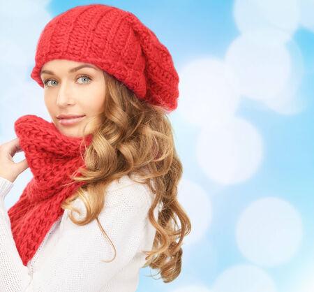 Glück, Winterurlaub, Weihnachten und Menschen Konzept - junge Frau im roten Hut und Schal über blauen Lichter Hintergrund