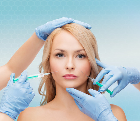 beauty, people and plastic surgery concept - woman face and beautician hands with syringes Stock Photo
