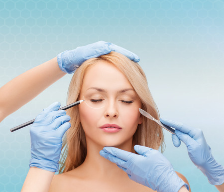 beauty, people and plastic surgery concept - woman face and beautician hands with marker and scalpel photo