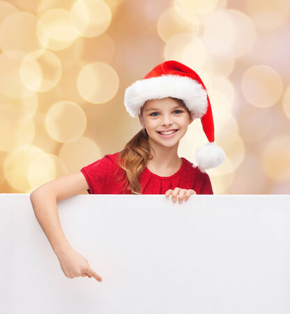 christmas, holidays, people, advertisement and sale concept - happy little girl in santa helper hat with blank white board over beige lights background photo