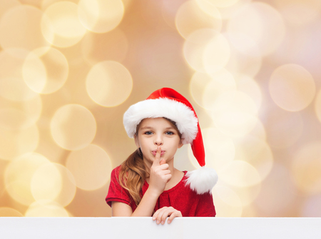 beige lips: christmas, holidays, childhood and people concept - smiling little girl in santa helper hat with finger on her lips over beige lights background