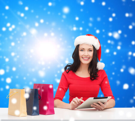 christmas, technology and people concept - smiling woman in santa helper hat with shopping bags and tablet pc computer over blue snowy background photo