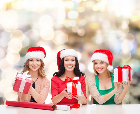 christmas, holidays, celebration, decoration and people concept - smiling women in santa helper hats with decorating paper and gift boxes over lights background photo
