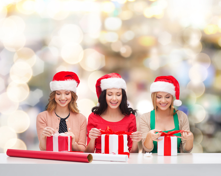 women in santa helper hats with decorating paper and gift boxes over lights background photo
