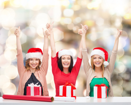 christmas, holidays, celebration, decoration and people concept - smiling women in santa helper hats with decorating paper and gift boxes showing thumbs up over lights background photo