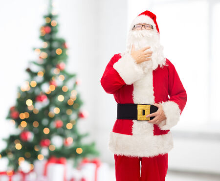 st  nick: christmas, holidays and people concept - man in costume of santa claus over living room and tree background