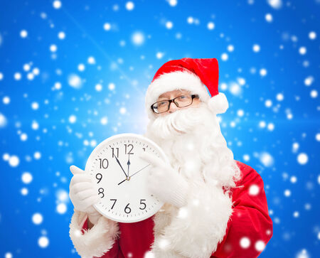 twelve month old: christmas, holidays and people concept - man in costume of santa claus with clock showing twelve over blue snowy background Stock Photo