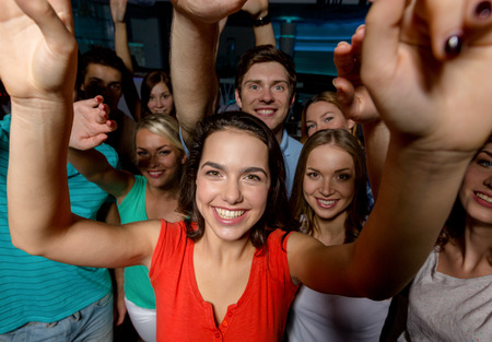 party, holidays, celebration, friends and people concept - smiling friends dancing and waving hands in club photo