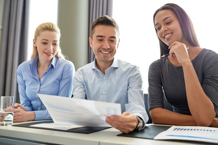 co workers: business, people and teamwork concept - group of smiling businesspeople meeting in office Stock Photo