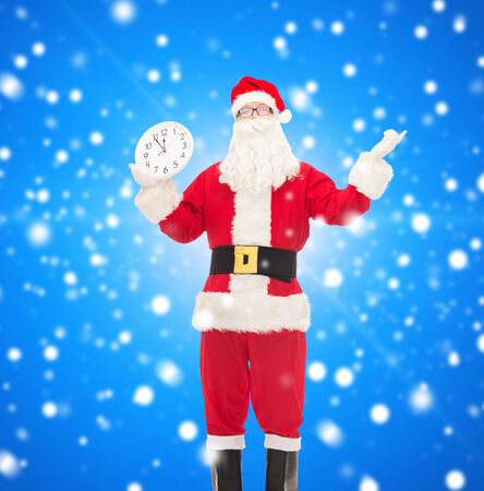 christmas, holidays and people concept - man in costume of santa claus with clock showing twelve over blue snowy background Stock Photo